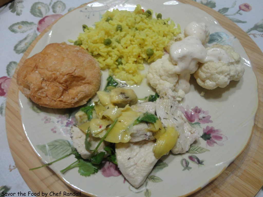 Plated Lemon Artichoke Chicken with accompanied sided dishes of rice ...