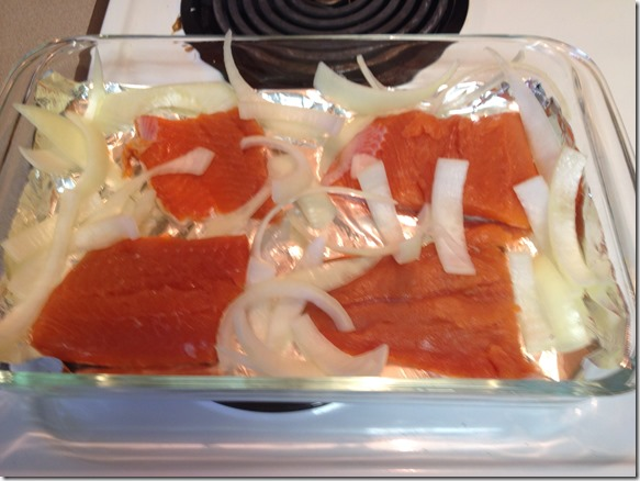 sliced onions adding to baking dish with Salmon