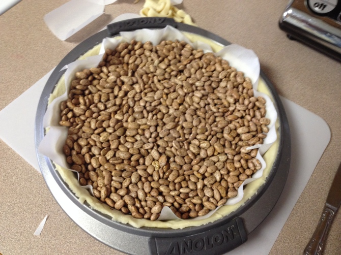 parchment and dried beans placed over crust