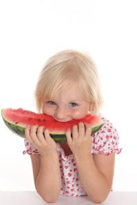 little girl enjoying a sweet watermelon