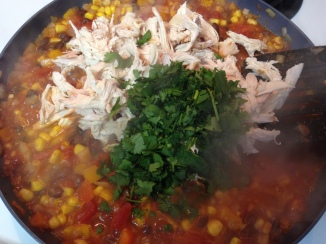 adding shredded chicken and cilantro to vegetable mix for Mexican Chicken Tortilla Pie