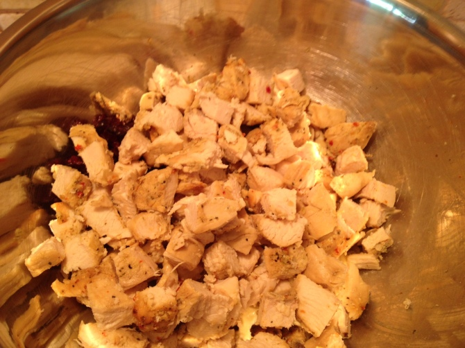 adding cooked chicken to other ingredients for Herb Chicken and Cranberry Almond Salad