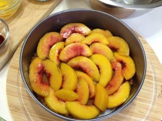 arranging peaches in uniform over brown sugar mixture