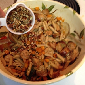 adding pecan pieces to Roasted Butternut Squash and Sausage with Gluten Free Penne Pasta