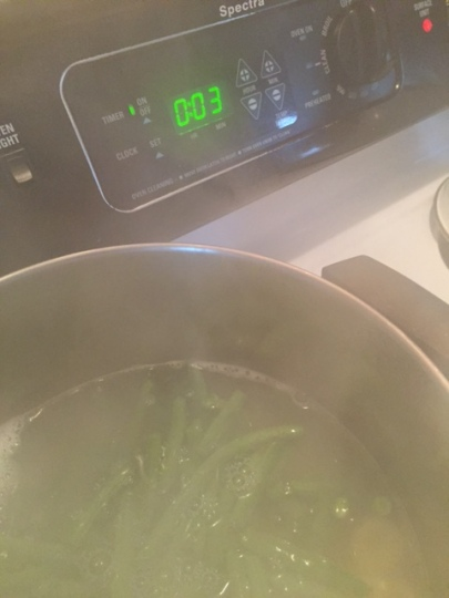 adding greens beans to pot of  boiling water with Orecchiette pasta