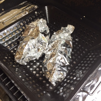 Foil wrapped BBQ Hotdogs and Potato Pack in a BBQ basket