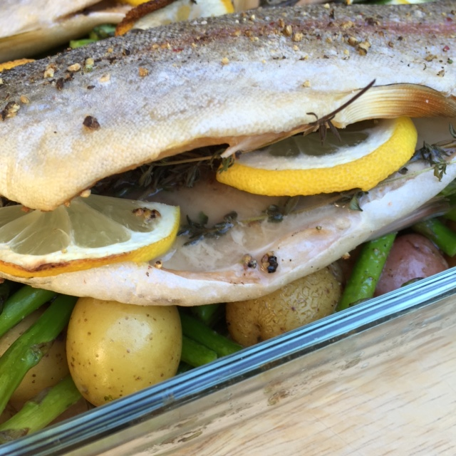 Fresh roasted trout showing the amazing flavors of freh thyme, cruched pepper corns and lemon slices