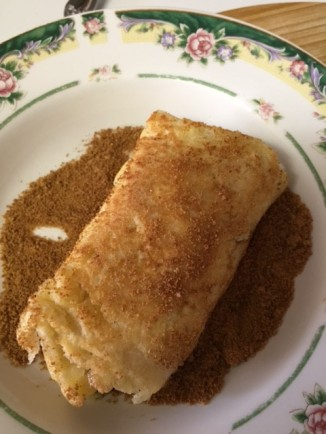 rolling cooked French Toast Fruit Roll Ups in coconut sugar