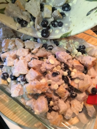 adding Blueberry White Chocolate Bread Pudding to a glass baking dish
