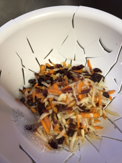 rinsing shredded carrots and dried cherries under running water
