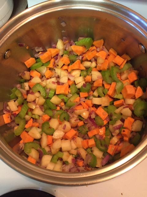 adding vegetables to garlic