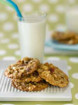 Power Packed Popcorn Cookies with a glass of milk in the back ground on a table