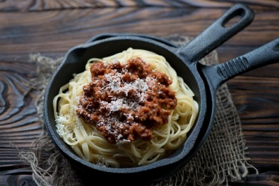 Close-up of spaghetti bolognese in a cast iron frying pan