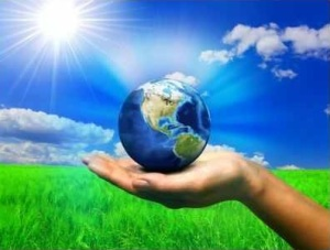 the earth in a woman's hand with green grass and blue sky in the back ground