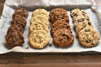 Closeup of a tray of fresh baked cookies, Chocolate Chip, oatmeal raisin Chocolate and white chocolate chip cookies on baking sheet and parchment paper -Baking Cookies Everyone Will Enjoy