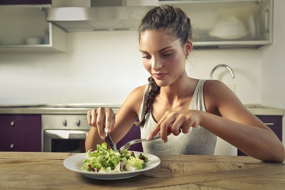An younf woman eating a warm winter salad
