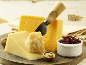 cheddar cheese on a cutting board with a small ceramic bowl of jam