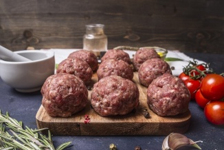 raw meatballs on a cutting board with vegetables and herbs on wooden rustic background - National Meatball Day