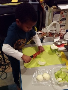 young boy learning to cut with a knife - Cooking Simple With Your Family