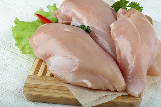 Raw chicken breast with peppers and salad leaves on the wood background