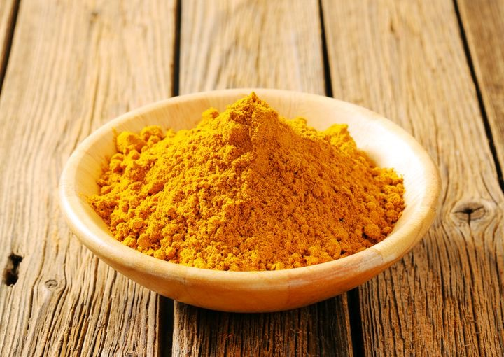 Bowl of curry powder on a wood deck