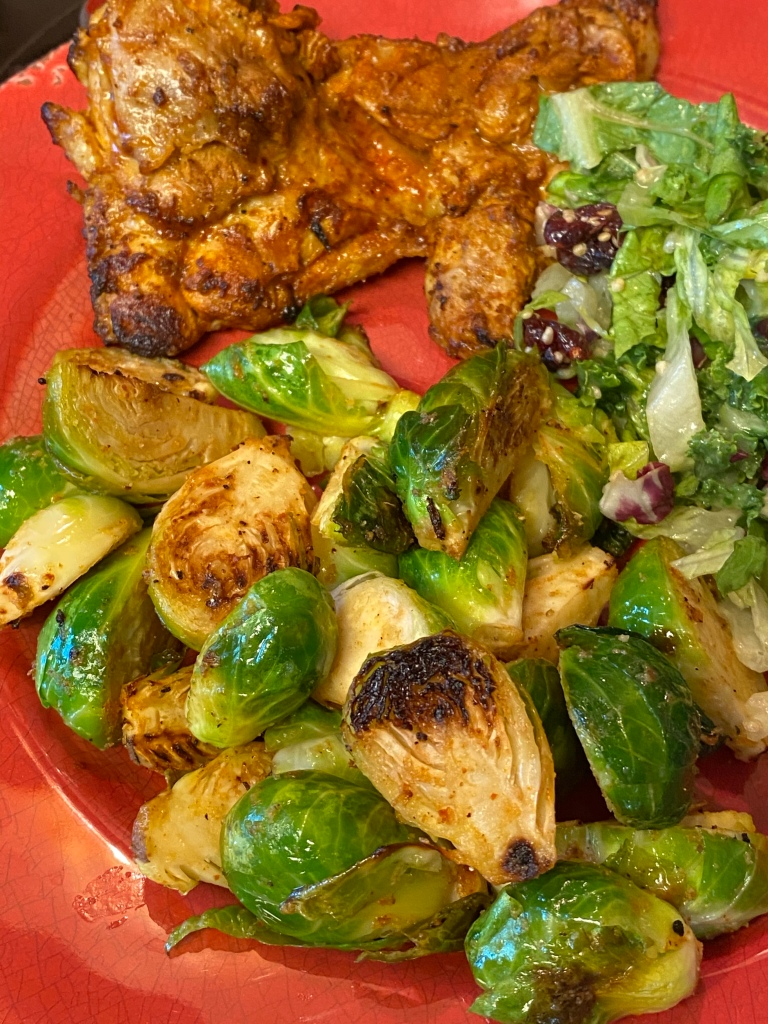 Platted grilled Brussels sprouts with chicken and salad